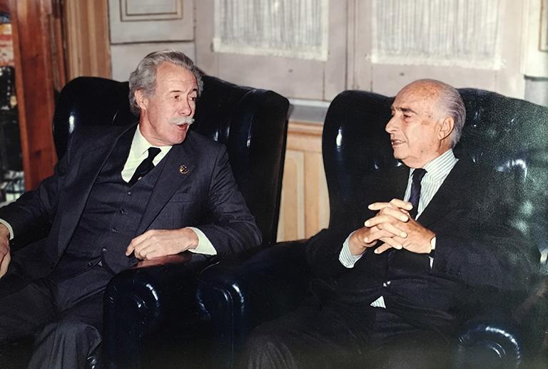 El multicampeón de Fórmula Uno, Juan Manuel Fangio, en la Sala Principal de Colegio charlando con John R. Vibart, luego de haber participado de una mesa redonda de Deportes